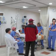 Dr. Powell and OR and Recovery team attend to the recovery of a PAO patient while her family member looks on.