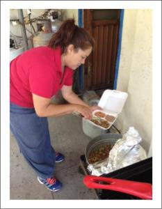 Sandra dishes up a hot meal to be delivered.