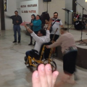 The woman could not walk before but pushed her own wheelchair after the Holy Spirit healed her.