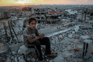 A boy sits amid the rubble of his destroyed house overlooking Gaza