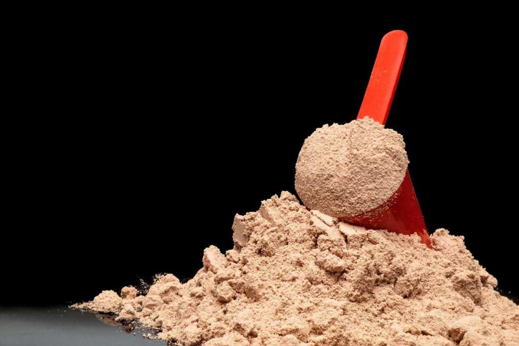 A picture of a pile of powder from a meal replacement shake bottle, with the scooper laying on top.