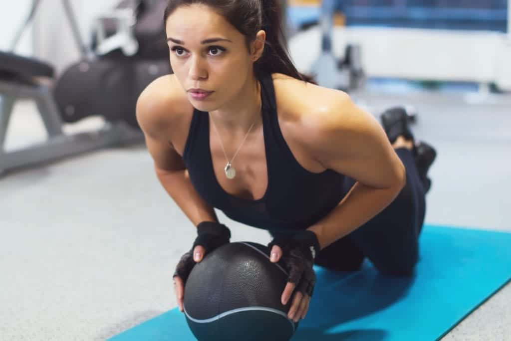 a young woman working out with a medicine ball, bodybuilding tips