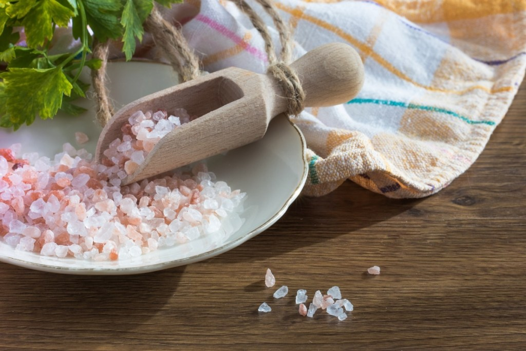A picture of sea salt inside of a white bowl and a wooden spoon. Saying no to salt is one of the 10 tips to a healthy diet