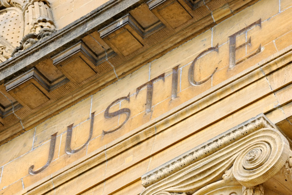 The word justice chiseled on the entrance of a court house, depicting what makes legal steroids legal.