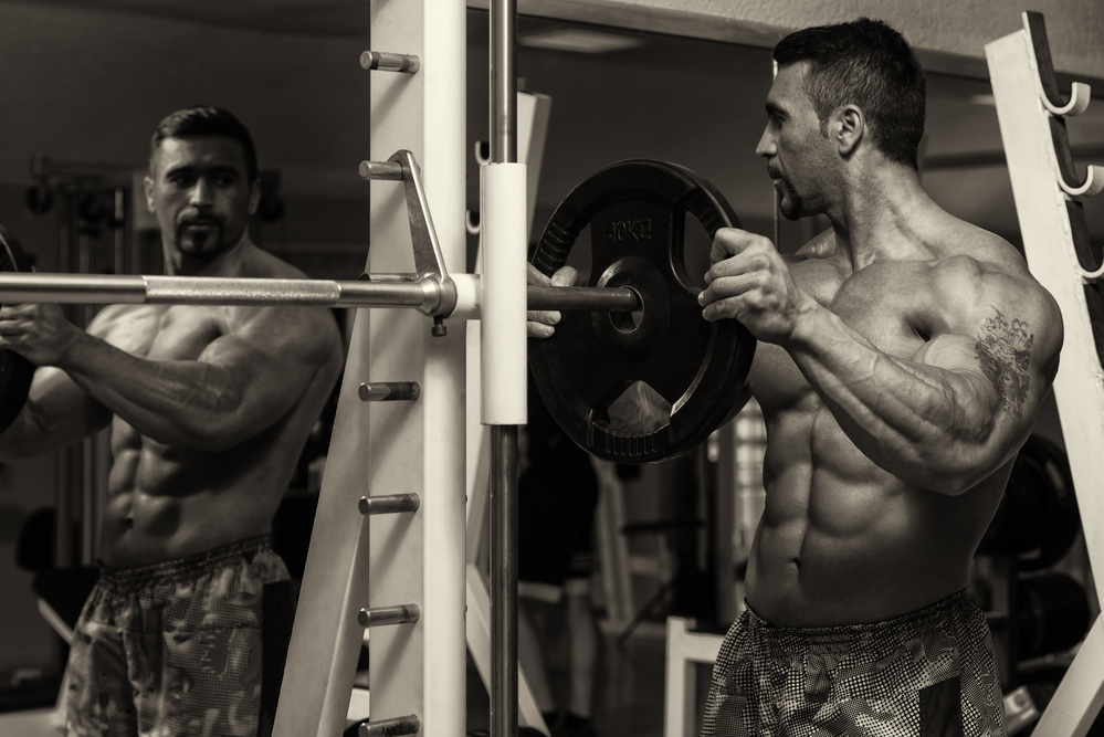 Body Builder Putting Weights On Bar In Gym after taking D-bal a legal steroid