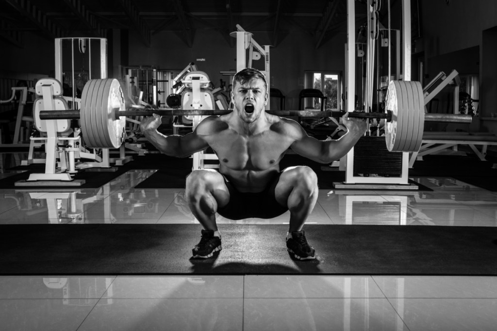 Man at the gym. Execute squat below parallel with weight, in gym