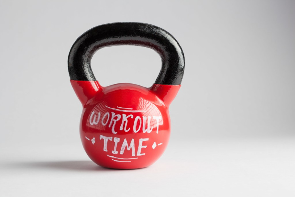 Red kettlebell with Workout Time lettering written on it isolated on white with copy space referring to when to take whey protein