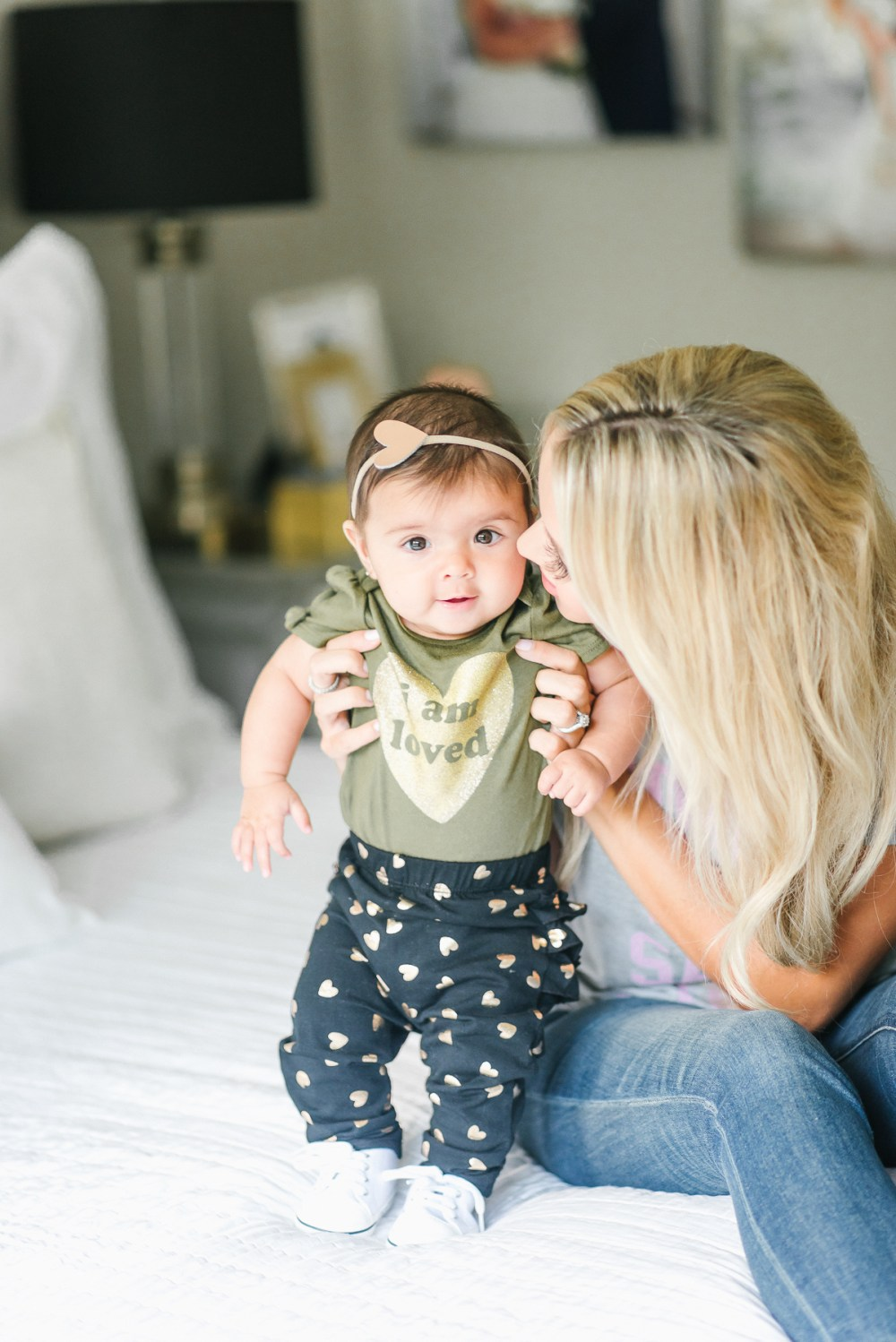 """My sweet baby girl in her """"I am loved"""" olive onesie and matching heart headband! All the heart eyes for this cutie! Mother and daughter!"""