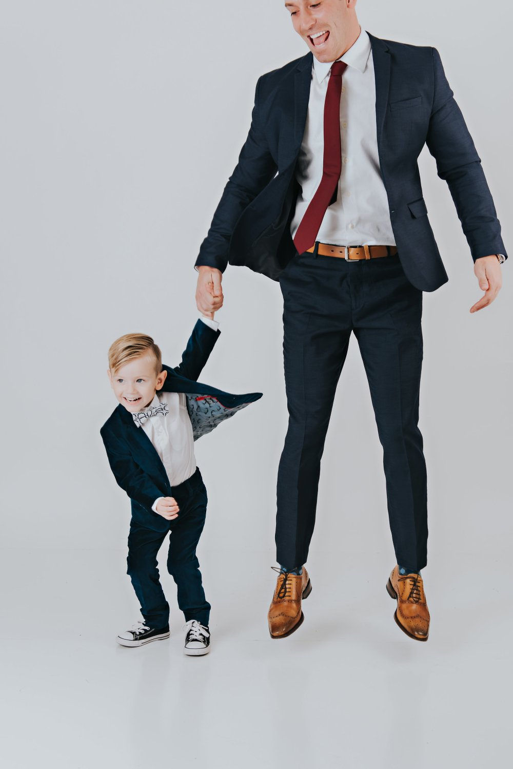 This photo is SO fun! Truly captures the energy these two put off! Both looking dapper in their suits! Perfect outfits for weddings, parties or any special occasion! #likefatherlikeson #sharpeddressedmen #boysfashion #mensfashion #familyphotos #candidphoto