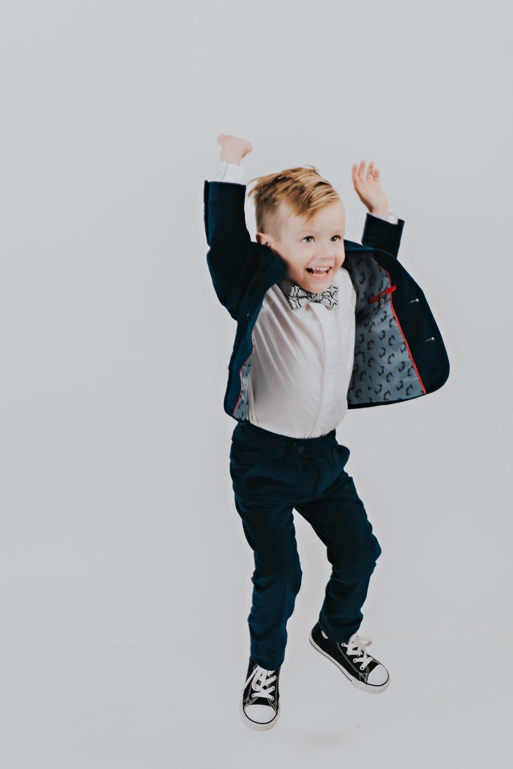 Isn't Truman so handsome?! I love his suit and bow tie! His outfit details are listed on the blog and great for any special occasion! #boysfashion #familyphotos #boysoutfitideas