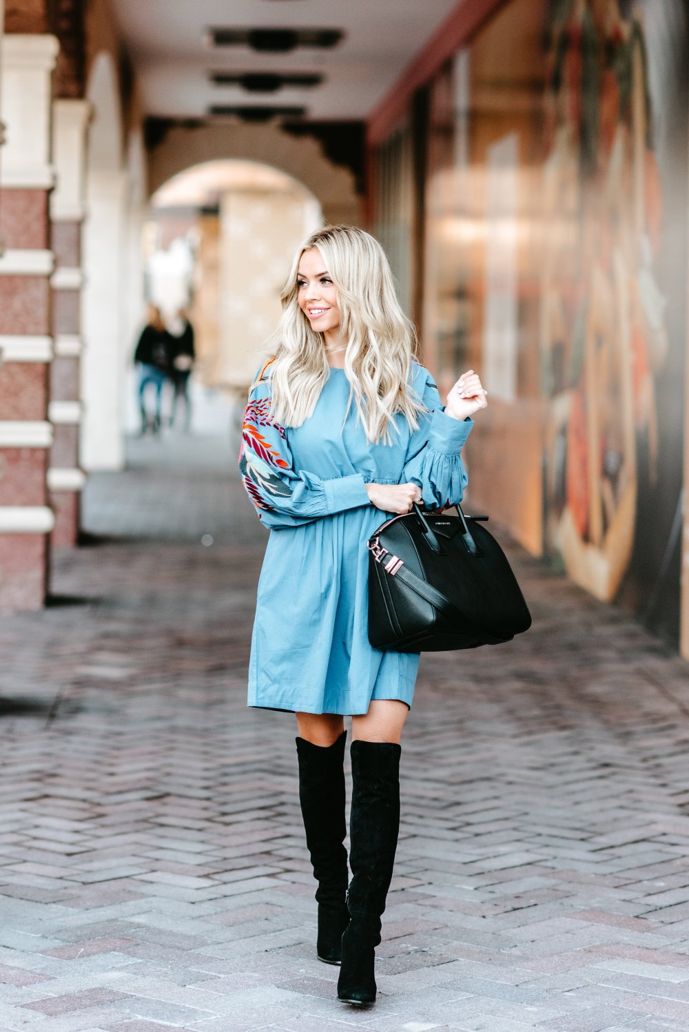 Over the knee boots are such a closet staple and are worth wearing through more than one season! Transition your OTK boots into spring with dresses like this one that can also be worn later in spring/summer with wedges or sandals! I am crushing on the pop of color in this outfit with the embroidery details! My over sized bag adds a touch of glam too! #trulydestiny #womensfashion #otkboots #embroidery #springfashion #transitionpieces