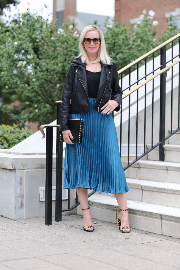Dallas style blogger wearing BlankNYC faux leather moto jacket, turquoise pleated midi skirt and carrying Valentino Rock Stud black clutch.