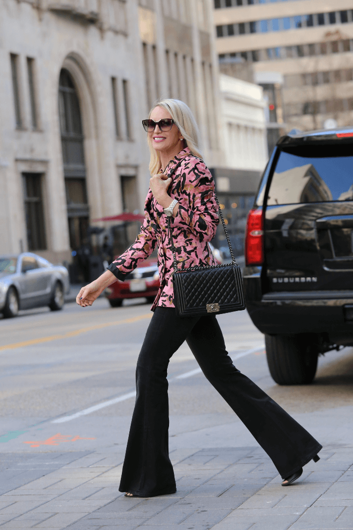 Dallas fashion blogger Megan Saustad of 'Truly Megan' wearing pink jacquard animal print blazer, black flare jeans, Prada sunglasses and carrying Chanel medium boy bag in black leather.