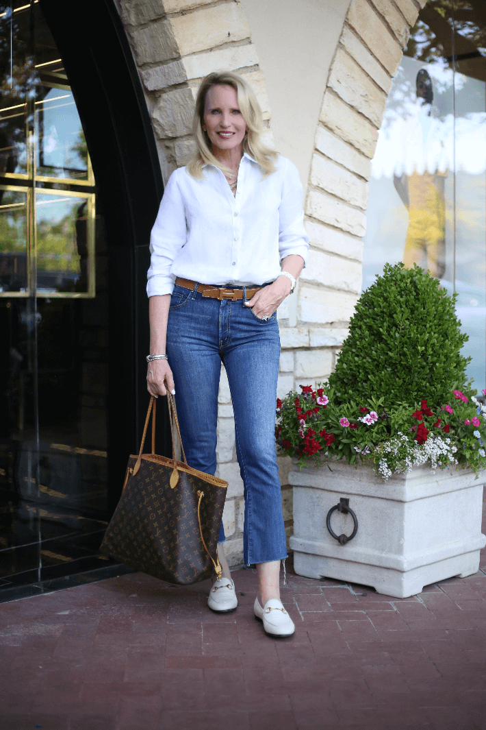 Dallas fashion blogger Truly Megan wearing white linen shirt, Hermes belt, Gucci loafers, and carrying Louis Vuitton Neverfull bag.