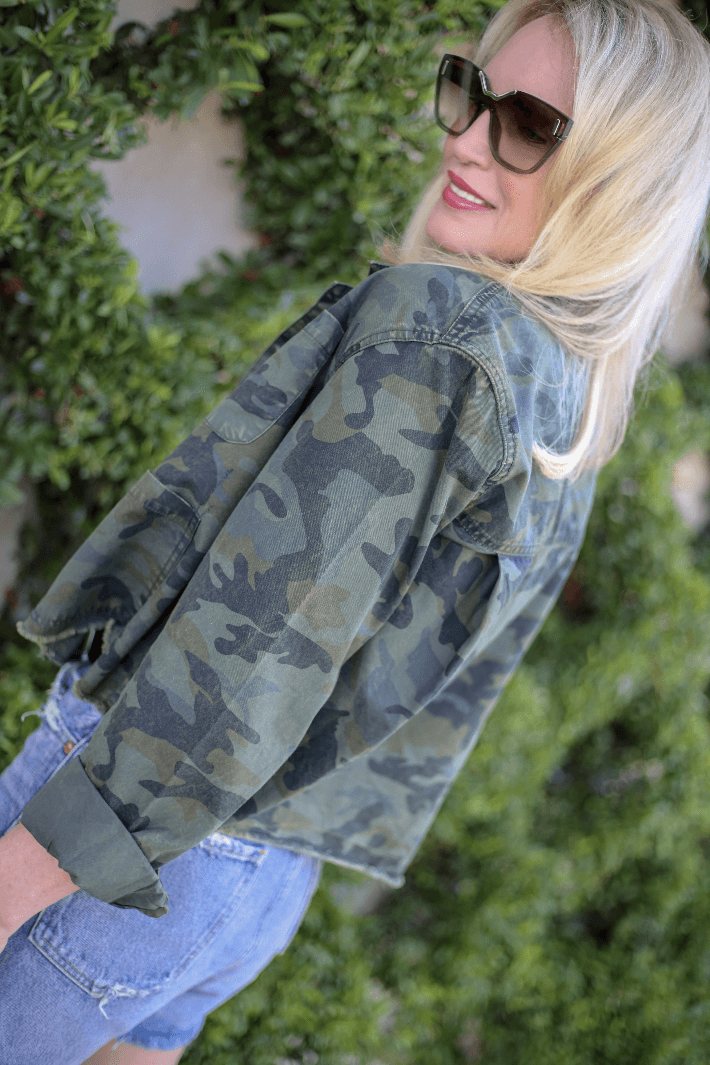 Style blogger Truly Megan wearing camo jacket and Agolde denim shorts.