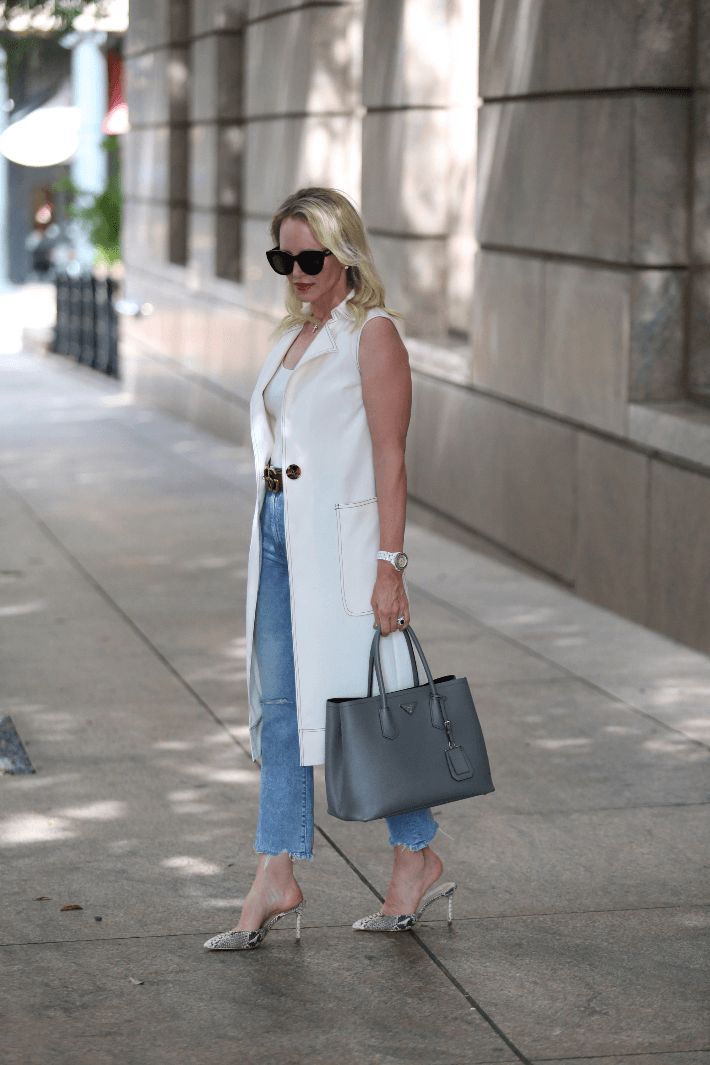 Dallas style blogger Megan Saustad wearing Topshop duster, Mother ankle fray jeans and carrying Prada handbag.