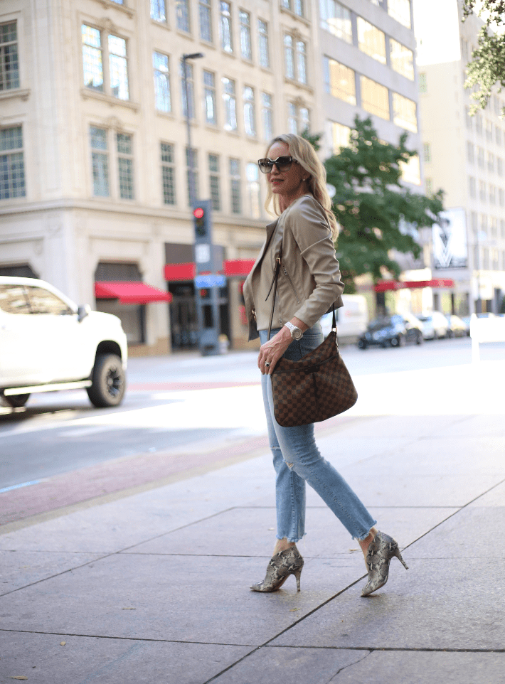 Dallas blogger Megan Saustad wearing BlankNYC faux leather moto jacket, Mother cropped denim jeans, snake print booties and carrying Louis Vuitton Damier Ebene Canvas Bloomsbury PM.