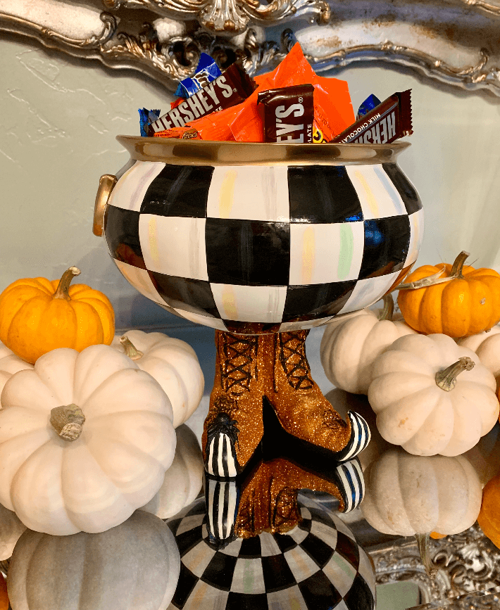 The Mackenzie Childs Courtly Checked Cauldron is filled with Halloween candy to greet guests.