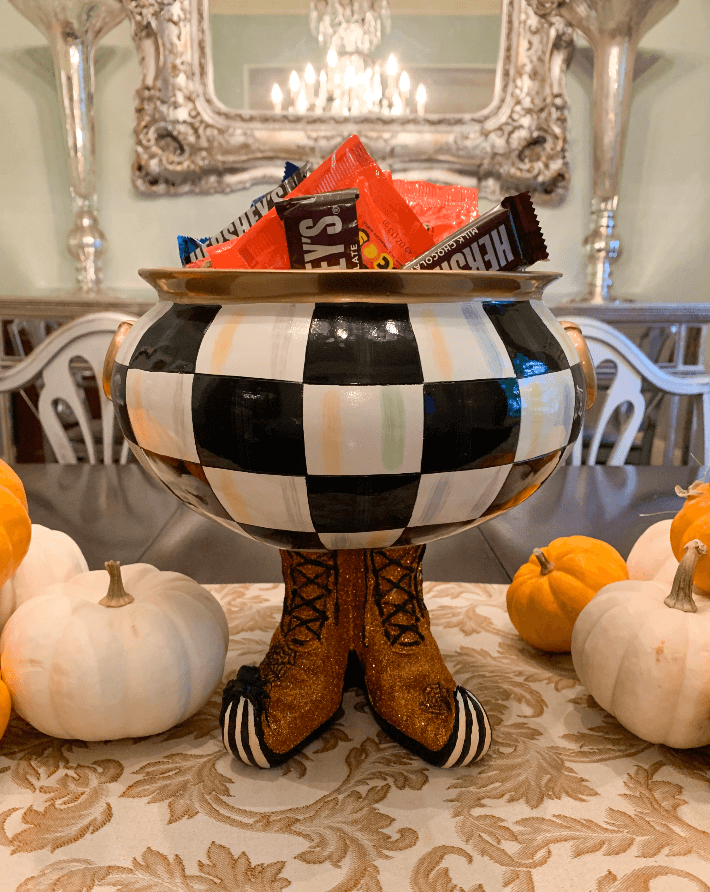 Lifestyle blogger Megan Saustad displays the MacKenzie Childs Halloween Courtly Checked Cauldron filled with candy.