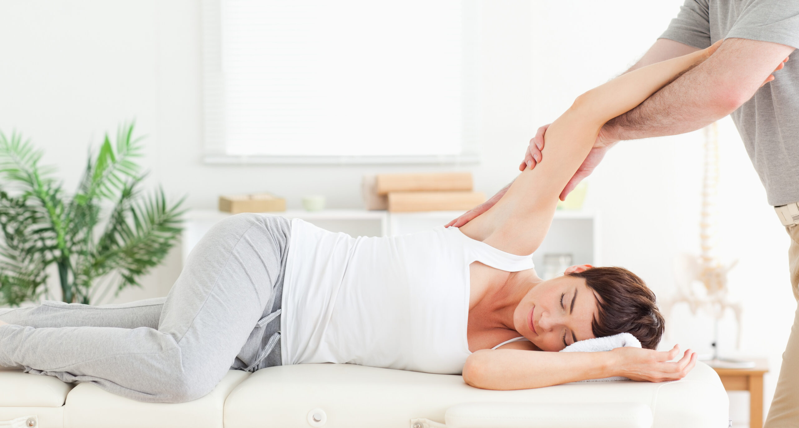 Massage therapist stretching woman's arm