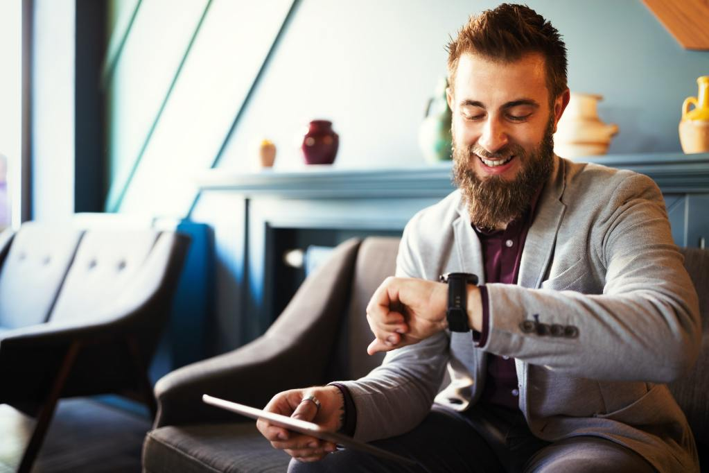 Business and time management concept. Happy business man looking at wrist watch