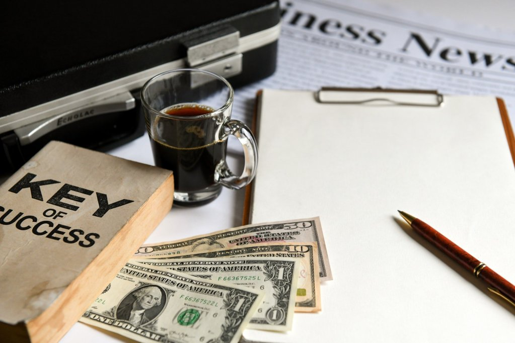 Key of success with notbook , briefcase , dollas and coffee.