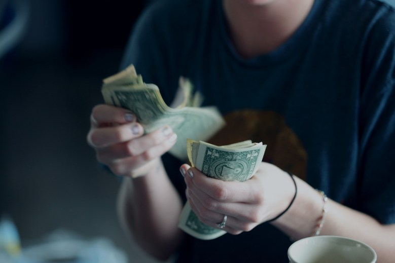 Woman counting one dollar bills to pay for cheap TEFL TESOL online certification course.