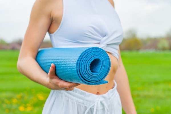 Woman holding rolled up yoga mat