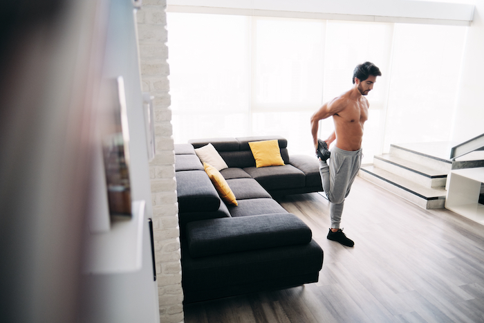 Man stretching and exercising in living room
