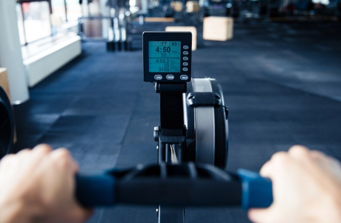 Hands pulling handle of a rowing machine