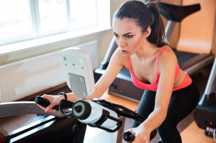Woman riding stationary spin bike at the gym