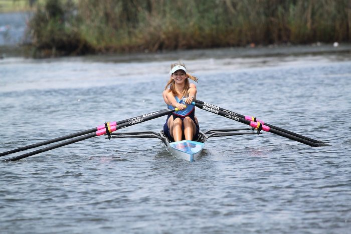 A female crew team rowing on the water