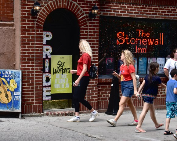 Pedestrians walk by a poster supporting sex workers displayed at The Stonewall Inn.