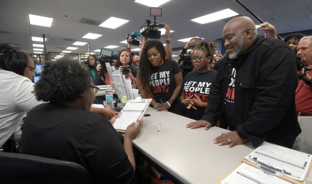 A man with his family registers to vote after ex-felons regained voting rights in Florida.