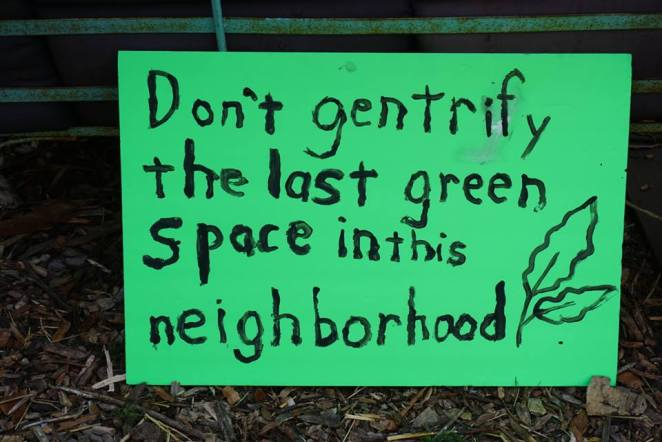 "A supporter makes a sign that says ""Don't gentrify the last green space in this neighborhood"" to support Bushwick City Farm in 2017."