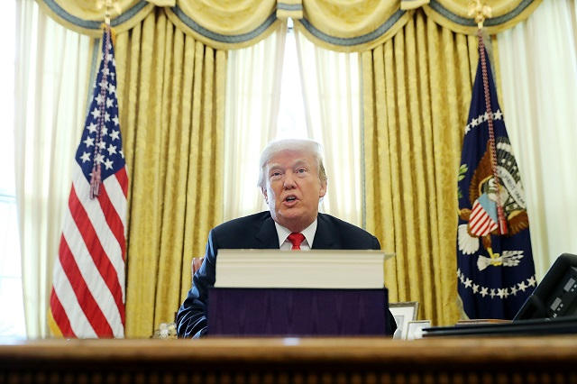 President Donald Trump talks with journalists after signing tax reform legislation into law in the Oval Office December 22, 2017 in Washington, DC. Trump praised Republican leaders in Congress for all their work on the biggest tax overhaul in decades. (Photo by Chip Somodevilla/Getty Images)