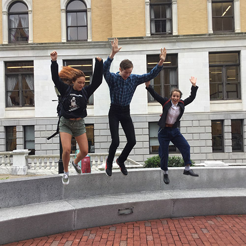 Teens Max Shannon, Madeleine Lombard and Aisling Jewett jump in the air outside the Massachusetts State House after delivering their testimony in favor of renewable energy