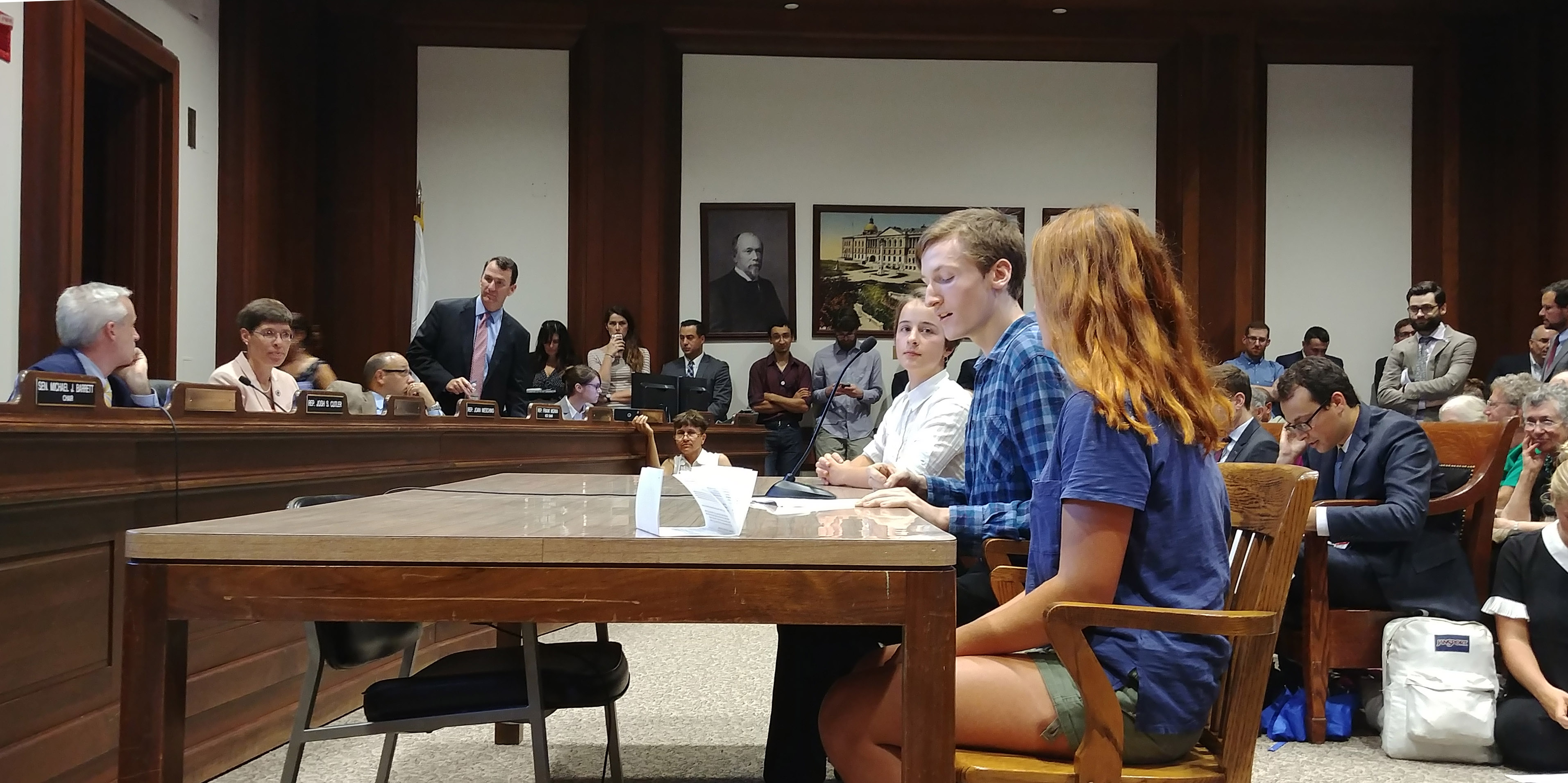 Max Shannon, flanked by Aislyn Jewett and Madeleine Lombard, speaking while seated at a table in front of lawmakers