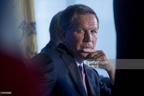 "John Kasich, governor of Ohio and 2016 Republican presidential candidate, waits to speak during a news conference outlining his national security strategy at the National Press Club in Washington, D.C., U.S., on Tuesday, Nov. 17, 2015. Kasich has said the U.S. should invoke the mutual defense article of the North Atlantic Treaty, increase collaboration by intelligence agencies with allies, and ""stem the flow of refugees into Europe"" by creating ""safe havens for civilian refugees on Syria's borders."" Photographer: Andrew Harrer/Bloomberg *** John Kasich"