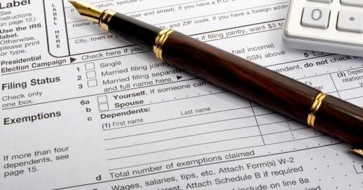 IRS tax form 1040 with fountain pen and calculator