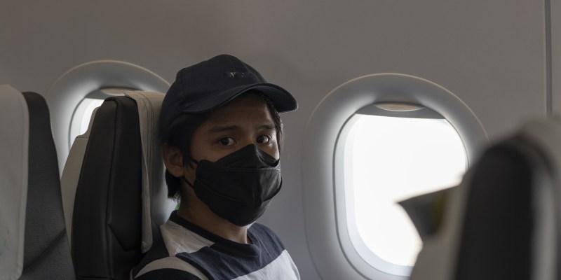 Passenger wearing face mask on airplane