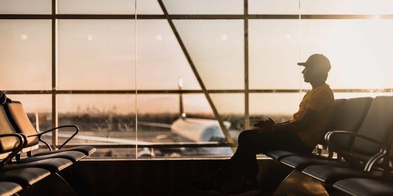 man sitting on gang chair near window