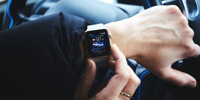 person holding gold aluminum Apple Watch