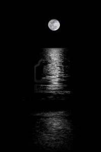 -full-moon-setting-on-the-horizon-in-the-ocean-with-reflection-shining-thru-black-and-white