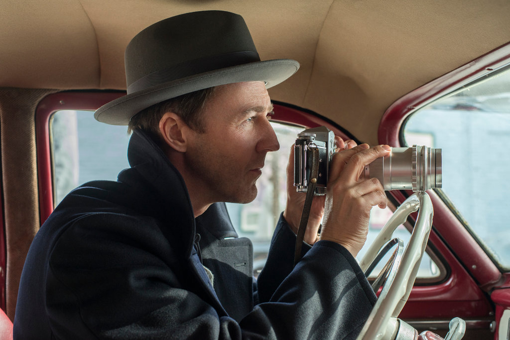 Photo of Edward Norton in Motherless Brooklyn, inside a car holding a camera.