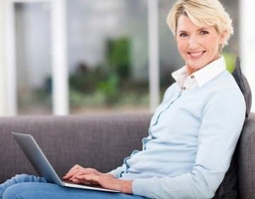 Middle aged woman on laptop sitting on couch