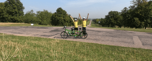 Lauren and John are stood behind their green tandem with windsor castle in the background