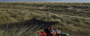 Looking down on our square, flat tarp set yp towards the grassy dunes out towards the sea.