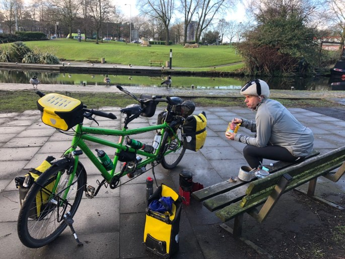 Picture shows our bike loaded with yellow bags next to a bench where John is eating some food. Geese can be seen next to the canal in the background.
