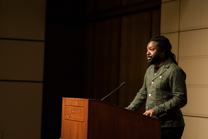 "Marlon James stands at a podium marked ""Claremont McKenna College"" at right"